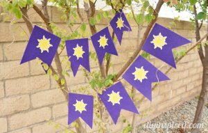 Purple banner with yellow suns hung in a tree for decorations for a Rapunzel party.